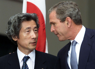Japan's Prime Minister Junichiro Koizumi (L) talls with US President George W. Bush prior to the fam..