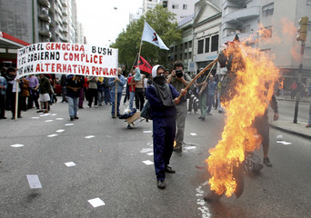 Demonstrators burn an effigy of U.S. President Bush to protest his visit to Uruguay in Montevideo
