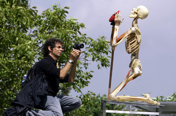 Man takes picture of a plastinated human body during a meeting on body donation for plastination in ...