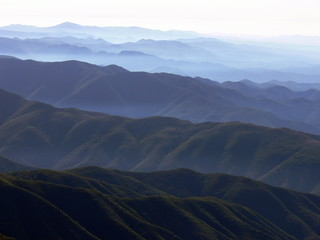 Saddleback mountain hills and valleys with haze