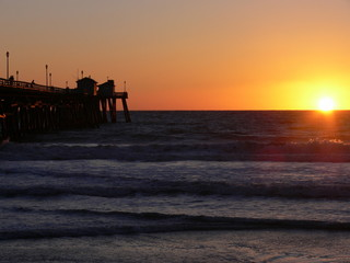 Ocean sunset with pier and waves