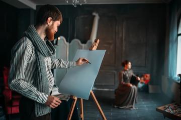 Painter drawing female portrait in art studio