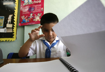 A visually impaired boy flips the pages of a book written in Braille at the Abel Santamaria school in Havana