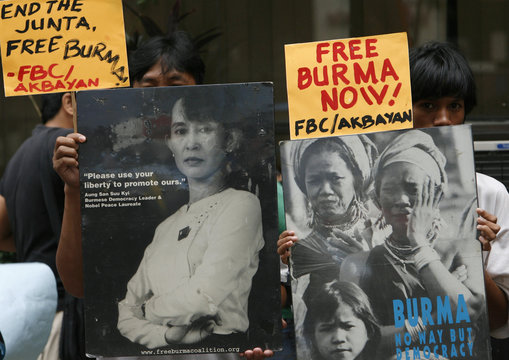 Protesters hold pictures of democracy icon Aung San Suu Kyi during a protest in front of the Myanmar embassy in Manila's financial district of Makati
