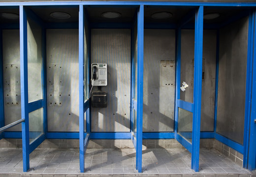 A single public pay telephone sits in a line of phone booths