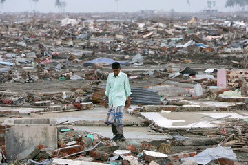 Acehnese resident Nyak Umar Ibrahim walks in the remains of his house washed out by the tsunami ...