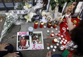 Fans light candles in front of old pictures of Michael Jackson in front of the U.S. embassy in Bucharest