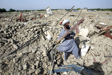 A PAKISTANI TRIBESMAN AHAMD JAN RETRIEVES ITEMS FROM THE RUBBLE OF HIS HOUSE DEMOLISHED BY ...