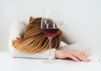 Drunk woman sleeping on the table. Female alcoholism.