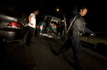 Federal police agents detain a man to search for drugs and weapons during a police operation in Monterrey