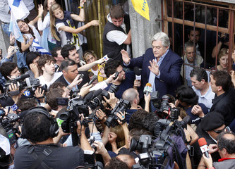 Nacional party candidate Luis Alberto Lacalle gestures to the crowd after casting his vote in Montevideo