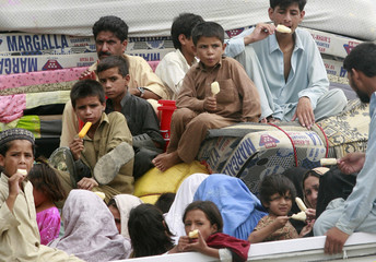 Internally displaced family eat ice cream in the back of a truck while returning home to their village by road through Malakand district