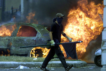 An anti-globalization protester strolls past a burning car as widespread clashes with police erupted..