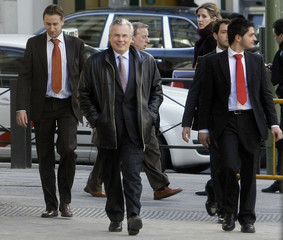 High Court magistrate Garzon walks with plainclothes police officers towards the entrance of the High Court in Madrid