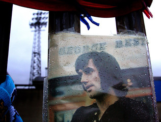 Rain drops are seen on a portrait of the Northern Ireland and Manchester United soccer legend Best in Belfast