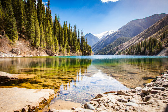 Majestic blue mountain lake with green trees