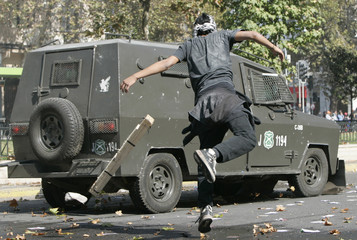 A demonstrator throws a stick against an armoured police car during May Day rallies in Santiago