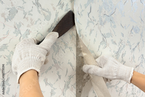Hands Removing Old Wallpaper With Spatula During Repair