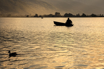 A man is fishing in a canoe at dusk