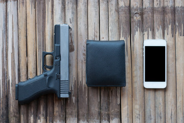 Gun pistol with Leather wallet and Smartphone on wooden background