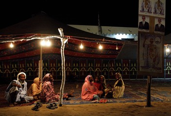 Mauritanians sit under a traditional tent awning beside election posters in Nouakchott