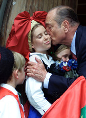 French President Jacques Chirac (R) kisses children dressed in traditional costumes as he leaves Col..