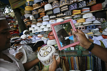 A customer tries on a prayer cap at the new market area in Dhaka
