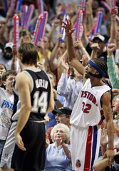 Spurs guard Udrih walks past Pistons guard Hamilton as he raises his hand to cheering fans in the ...