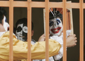 A Peruvian inmate wearing a joker costume looks at himself in a mirror after a ceremony marking Resocialization Day at the Castro Castro prison in Lima