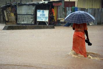 A woman holds an umbrella as she walks through torrential floods in Freetown