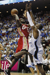 Cleveland Cavaliers' LeBron James goes up against the defense of Orlando Magic's Dwight Howard in the fourth quarter