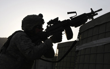 U.S. soldier of Gator Company, 2-12 IN, 4th Bgd fires a machine gun from Michigan Base in the Pech Valley