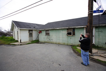 Tourist takes photograph of house left on intersection by floodwaters of Hurricane Katrina in Ninth Ward of New Orleans