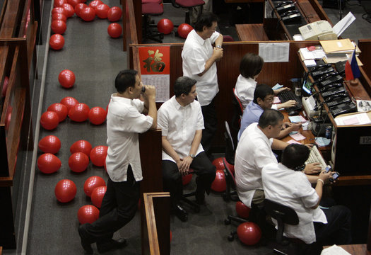 Red Balloons, left over from a visit from the Philippine President, clutter the floor of the Philippine Stock Exchange while traders man their desks in Manila's financial district of Makati