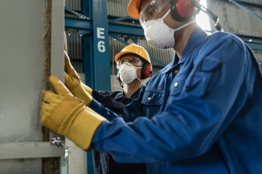 Two blue-collar workers wearing protective equipment