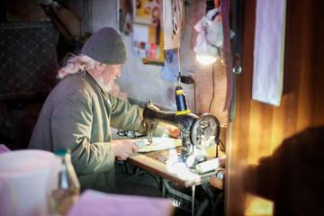 Old man working on sewing machine
