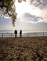 A couple is silhouetted as they enjoy a sunny autumn morning in Lindau