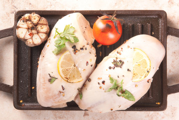 Grilled chicken breast during frying. With lemon, greens and garlic on the brazier for grilling. On old rustic wooden table. Top view copy space