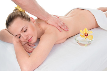 Side view of an attractive young woman receiving back massage at spa saloon