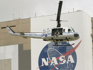 A NASA security helicopter containing officer with an automatic weapon flies over the crew of the space shuttle Discovery driving out to the pad at the Kennedy Space Center in Cape Canaveral