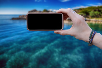 Woman using smartphone to take a picture of green tropical island. Vintage style. The screen is black