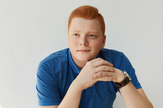 An elegant young handsome man with red hair and freckles wearing blue shirt and watch holding his hands together isolated over white background dreaming about something looking into distance