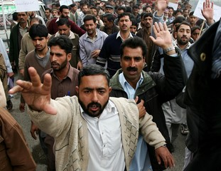 Kashmiri earthquake survivors chant slogans during a protest rally in Muzaffarabad