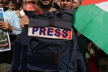 Palestinian mourner carries flak jacket of Reuters cameraman Fadel Shana during his funeral in Gaza City