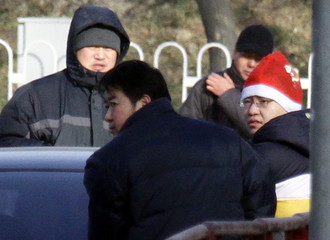 A supporter of one of China's most prominent dissidents Liu Xiaobo wearing a Christmas hat is led away from journalists by policemen outside the courthouse in Beijing