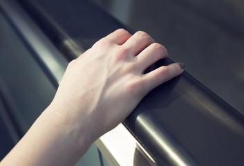 A female hand holds an escalator railing