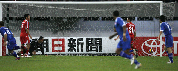Thailand's players watch as the goal scored by Singapore's Noh Alam Shah enters the net in Singapore