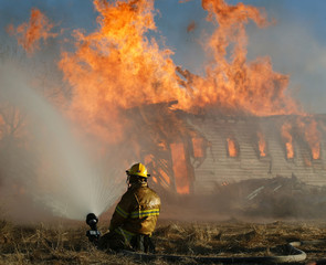 A fire fighter wets the grass surrounding an old prairie barn after lighting the old prairie landmark on fire for a training exercise near Chestermere.