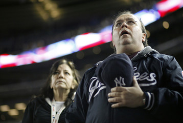 Fans sing during the seventh inning stretch during the game between the Yankees and the Cubs at Yankee Stadium in New York