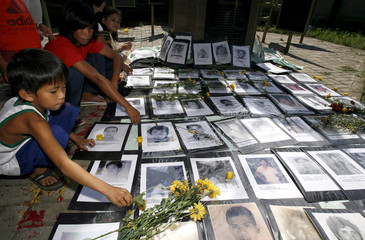 Family members place flowers in front of pictures of their missing loved ones in Manila